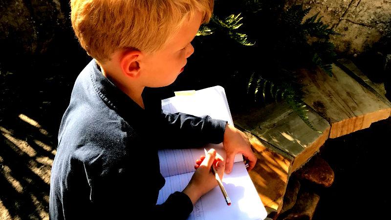 Foto von Junge mit Schreibblock
